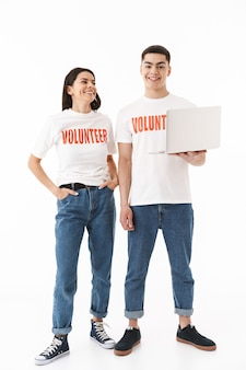 Full length portrait of a young attractive couple standing isolated over white wall, wearing volunteer t-shirts, using laptop