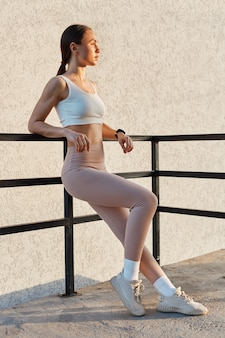 Full length portrait of young attractive female with confident facial expression wearing white top and beige leggins