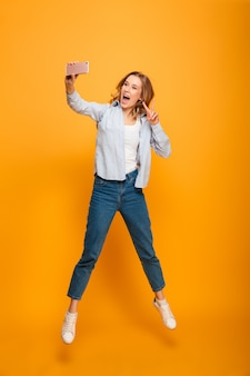 Full length portrait of young attractive woman smiling and showing victory sign while taking selfie with cell phone, isolated over yellow space