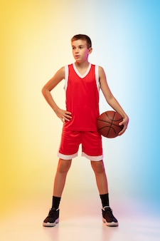 Full length portrait of young basketball player in uniform on gradient wall