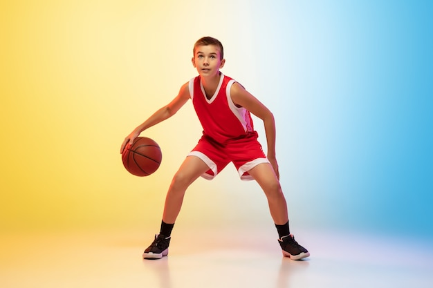 Full length portrait of a young basketball player with ball on gradient wall