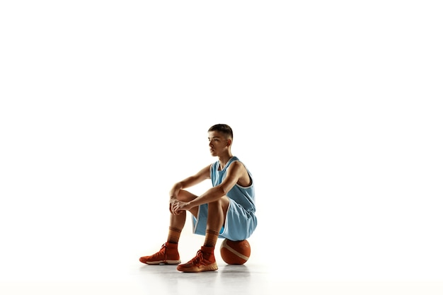 Full length portrait of young basketball player with a ball isolated on white  space
