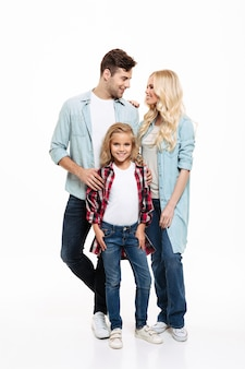 Full length portrait of a young beautiful family standing together