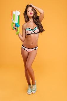 Полная длина портрет молодой красивой сексуальной женщины в бикини, держащей водяной пистолет и позирующей изолированной на оранжевом фоне