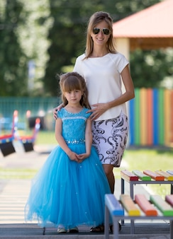 Full-length portrait of young blond slim smiling happily mother in sunglasses and small pretty daughter girl in long blue evening dress on kindergarten blurred playground.
