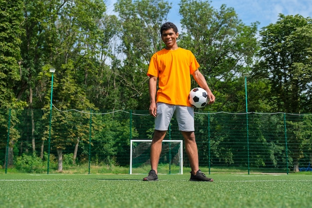 Full length portrait of young brazilian man holding soccer ball while standing on sports court outdoors against soccer goal
