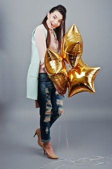 Full-length portrait young brunette girl wearing in pink blouse, turquoise jacket, ripped jeans and cream shoes holding gold star balloons.fashion studio shot