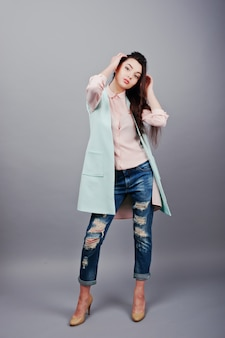 Full-length portrait young brunette girl wearing in pink blouse, turquoise jacket, ripped jeans and cream shoes