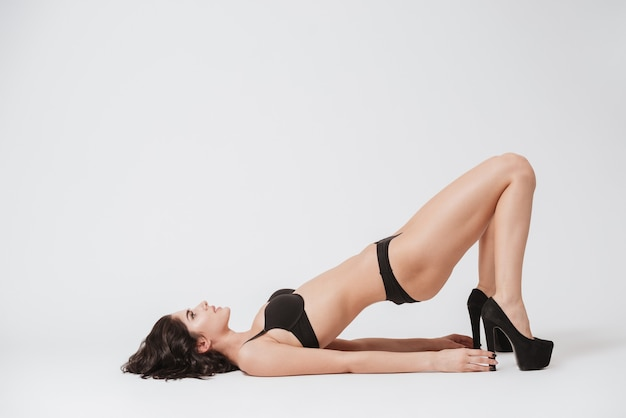 Full length portrait of a young brunette woman in lingerie and high heels shoes laying on her back isolated