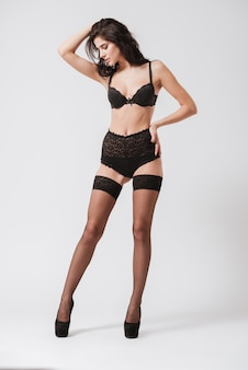 Full length portrait of a young brunette woman in lingerie posing and looking away isolated