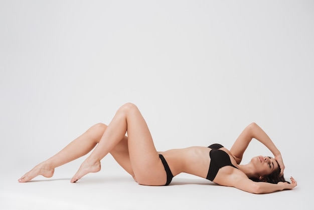 Full length portrait of a young brunette woman resting on her back with eyes closed on white surface