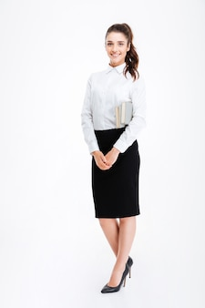 Full length portrait of a young business woman holding books isolated on white wall