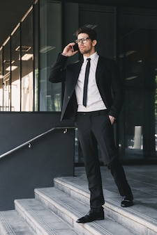 Full length portrait of young businessman dressed in formal suit standing outside glass building, and talking on cell phone