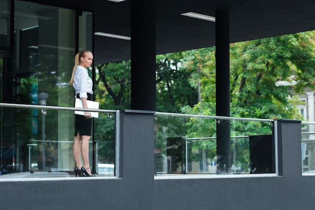 Full length portrait of a young businesswoman holding laptop standing at the glass building