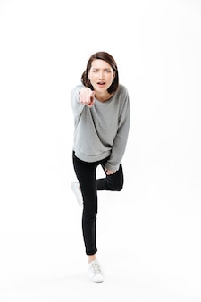 Full length portrait of a young casual woman standing on one hand and pointing finger