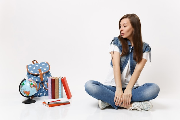 Full length portrait of young casual woman student in denim clothes sitting looking on globe, backpack, school books isolated