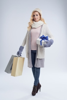 Full length portrait of young caucasian woman shopping for gifts