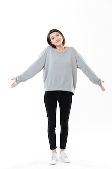 Full length portrait of a young cinfused woman shrugging shoulders