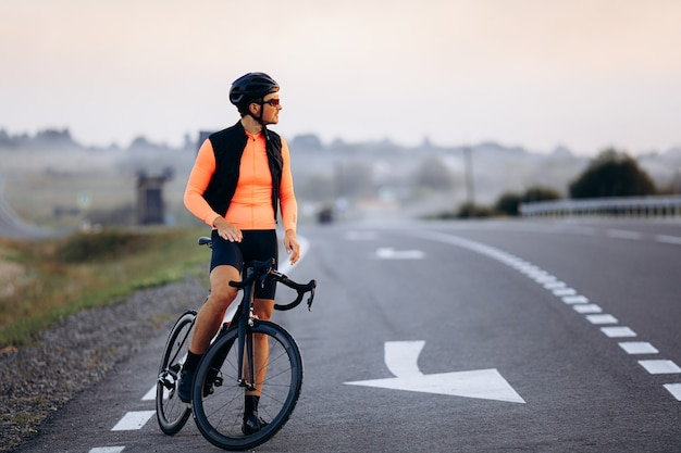Full length portrait of young cyclist in bright sport outfit riding bike during evening time