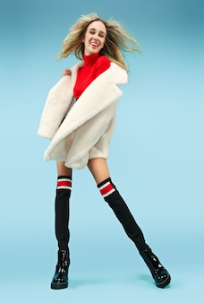 Full-length portrait of young elegant blonde funny woman at studio. female fashion and shopping concept.