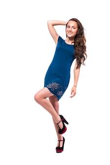 Ritratto integrale di giovane femmina in vestito blu che sta con la sua mano sulla vita isolata su fondo bianco