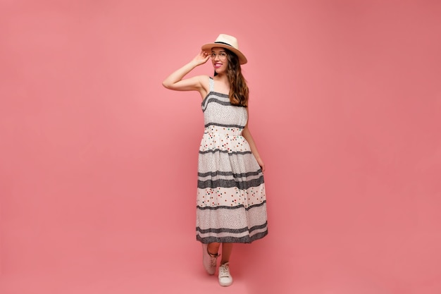 Full-length portrait of young female model in trendy dress dancing in studio with happy smile