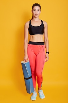 Full length portrait of young female with blue exercising mat in hand, posing isolated over yellow background