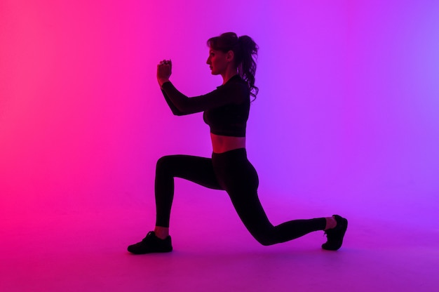Full length portrait of a young fitness woman doing squatting isolated on a vibrant colors background
