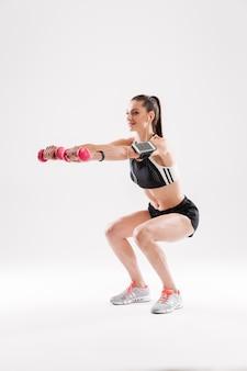 Ritratto integrale di una giovane donna di forma fisica in abiti sportivi