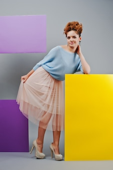 Full length portrait of young girl near art colored blanks.