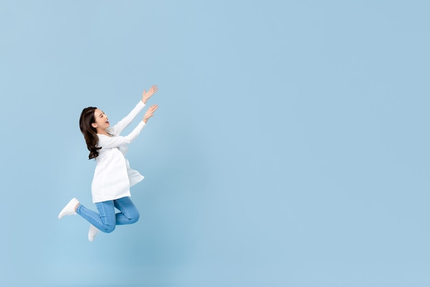 Full length portrait of young happy asian woman floating in mid-air with hands opening to copyspace beside in blue isolated wall