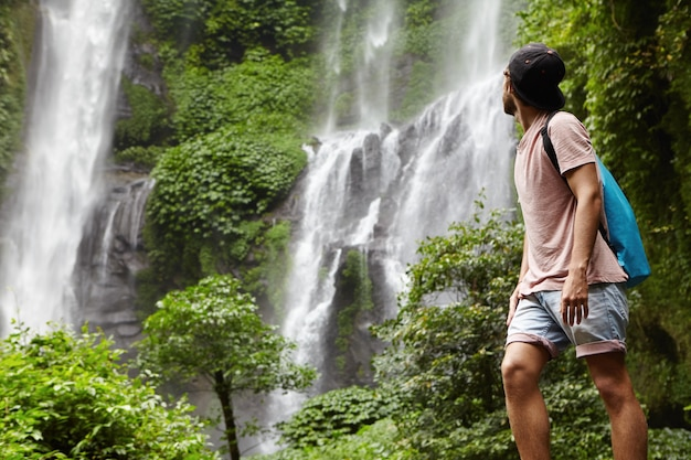 Full-length portrait of young hiker or adventurer in denim shorts and snapback enjoying nature