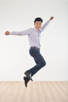 Full length portrait of young man jumping full of happiness