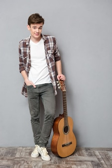 Full length portrait of a young man standing with guitar on gray wall