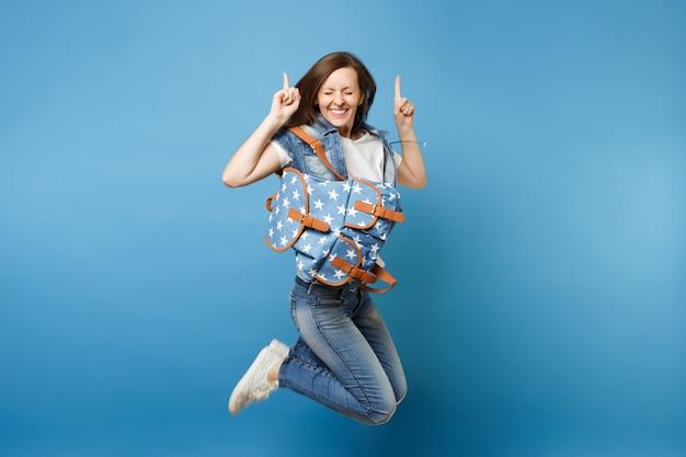 Полнометражный портрет молодой очень обрадованный студент женщины с закрытыми глазами с рюкзаком скача указывая фигеры индекса вверх изолированные на голубой предпосылке. обучение в средней школе. скопируйте место для рекламы.