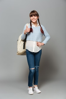 Full length portrait of a young schoolgirl with backpack