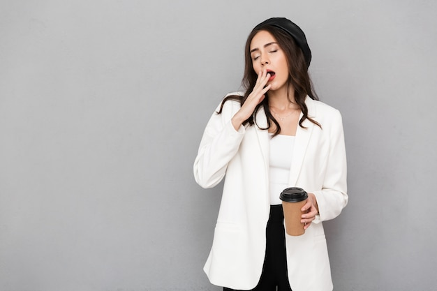 Full length portrait of a young sleepy businesswoman over gray background, holding takeaway coffee, yawning