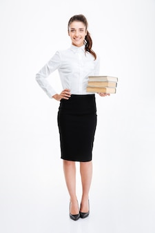 Full length portrait of a young smiling business woman holding books isolated on white wall