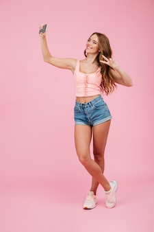 Full length portrait of young smiling readhead woman in summer wear makes selfie on smartphone, showing peace sign