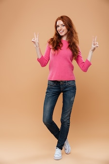 Full length portrait of a young smiling redhead girl with victory hand gesture