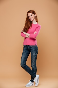 Full length portrait of a young smiling redhead girl