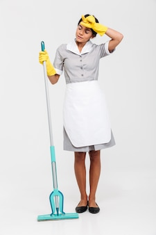 Full length portrait of young tired woman in uniform holding mop and wipes sweat from her forehead