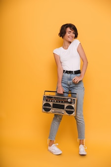 Full length portrait of a young woman holding record player