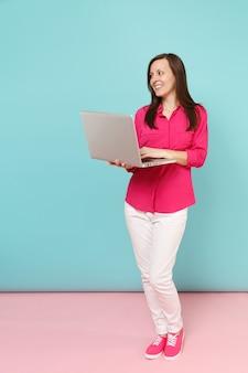 Портрет молодой женщины в полный рост в розовой рубашке, блузке, белых штанах, держащей портативный компьютер, изолированной на ярко-розовой голубой пастельной стене.