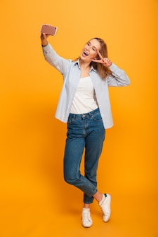Full length portrait of young woman smiling and showing peace sign while taking selfie with cell phone, isolated over yellow space