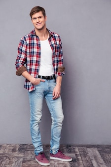 Full length potrait of charming happy young man in plaid shirt standing isolated over grey wall