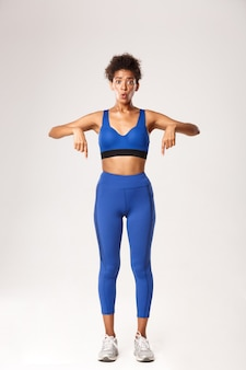 Full length of pretty african-american sportswoman looking wondered, pointing fingers down, wearing