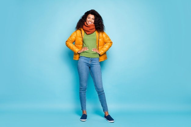 전체 길이 꽤 어두운 피부 곱슬 아가씨 산책 여행자 착용 유행 노란색 가을 외투 청바지 녹색 풀오버 절연 파란색 벽에 밖으로 나가는 좋은 봄 분위기