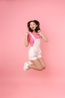 Full length of a pretty excited young teenage girl jumping isolated, rejoycing, pointing away