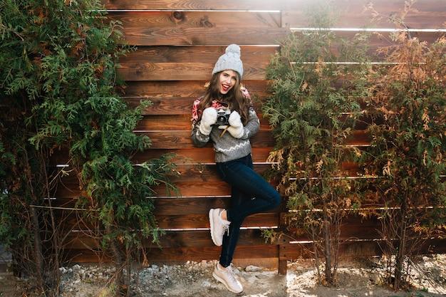 Ragazza graziosa integrale con capelli lunghi in cappello lavorato a maglia e guanti che tengono la macchina fotografica su legno.